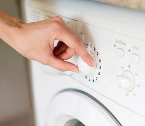 Frau die einen Waschtrockner bedient.