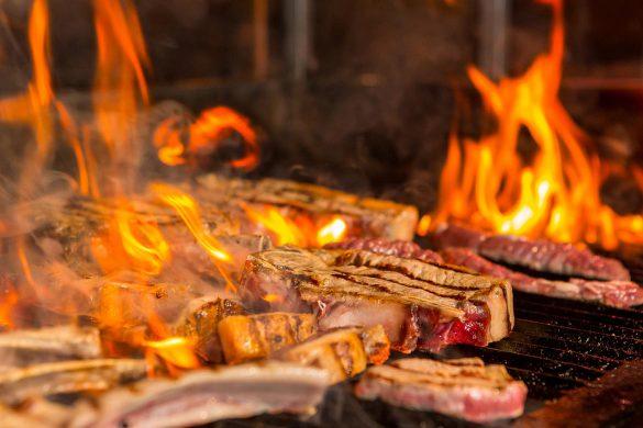 Steak das auf einem Oberhitzegrill brutzelt.