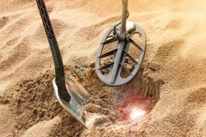 Schatzsuche mit Metalldetektor und Pinpointer im Sand.