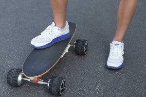 Junger Mann auf einem Elektro Skateboard.