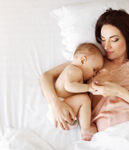 Junge Mutter die ihr Baby mit Stillhütchen stillt.