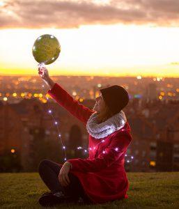 Frau lässt einen Ballon mit einer LED-Lichterkette steigen.