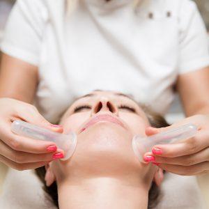 Frau wird anhand der Schröpfgläser Massage behandelt.
