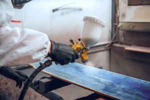 Maler der mit einer Druckluftpistole Holz färbt.