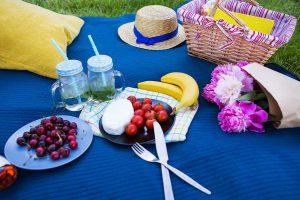 Gemütliches Sommerpicknick auf einer blauen Picknickdecke.