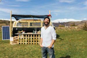 Gute gelaunter Camper vor seinem autarken Campingbus.
