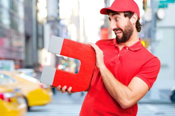 Mann hält einen großen Magnet in der Hand.
