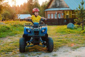 Kleiner Junge fährt auf einem Pocketbike Quad durch den Garten.